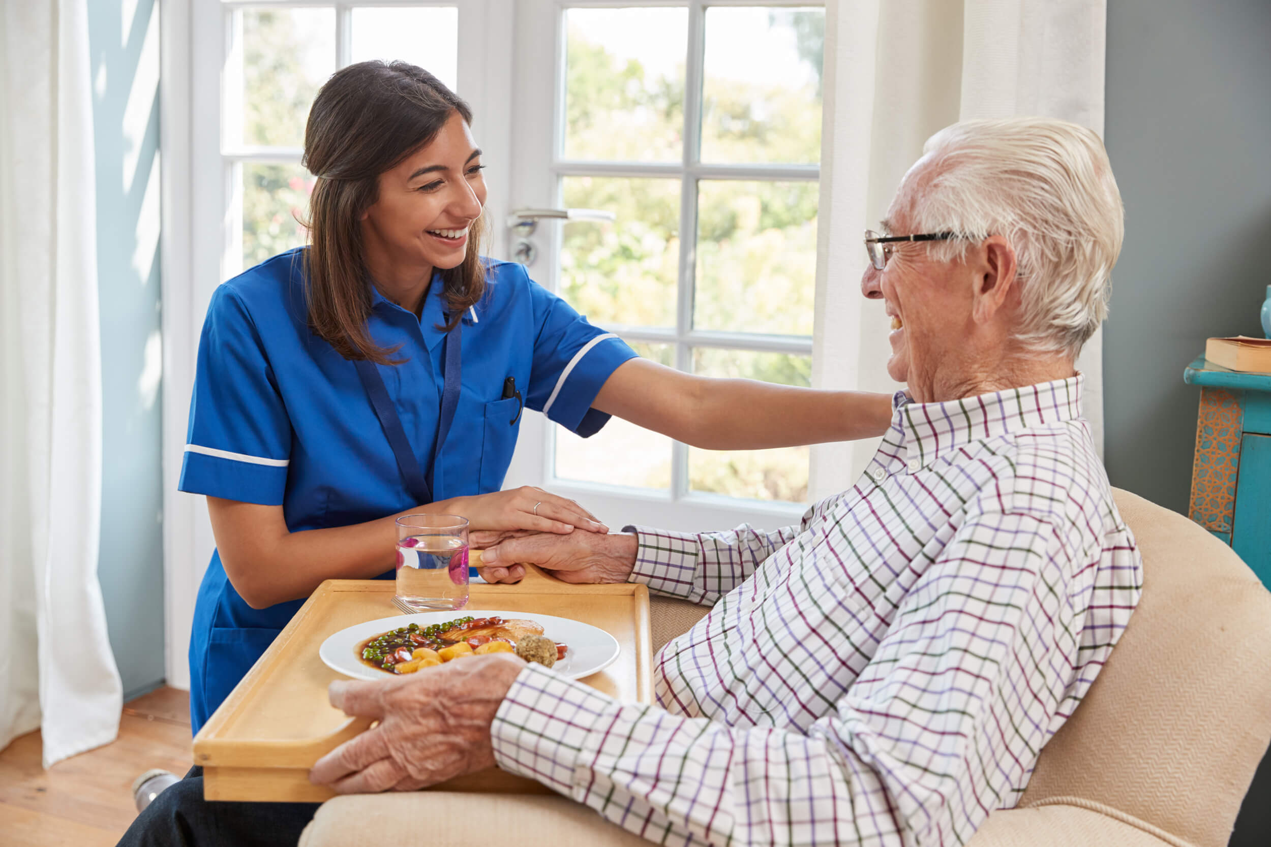 UK Caring Services Nurse serving dinner to a senior man in an armchair at home